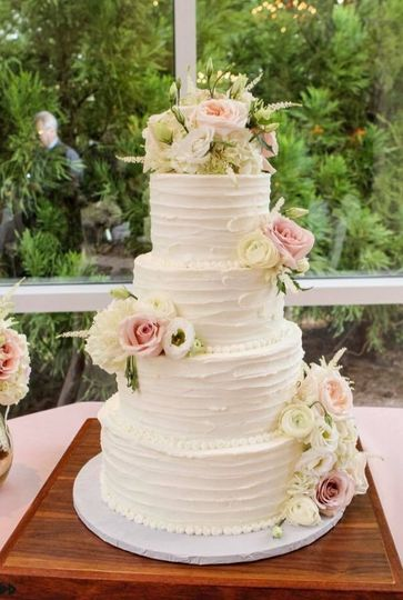 White wedding cake with soft colored flowers