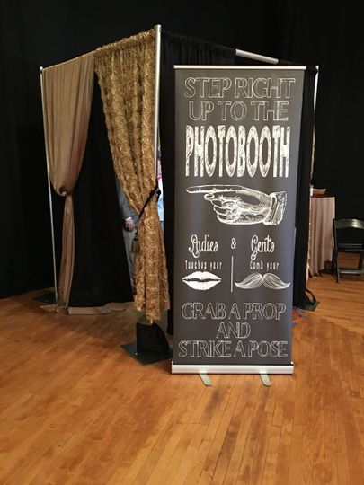 An example of an enclosed photo booth and a photo booth sign.