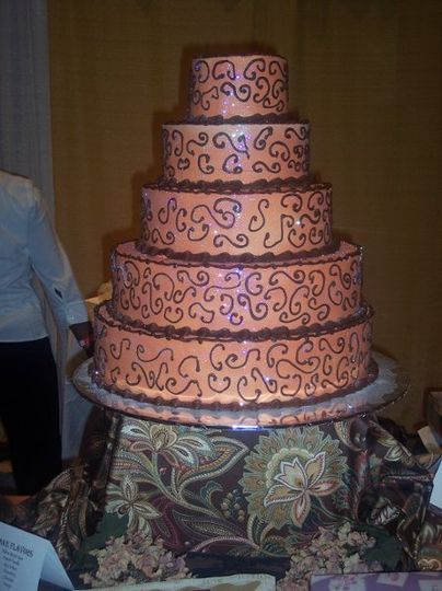 5 tier peach colored wedding cake with chocolate scrolls.