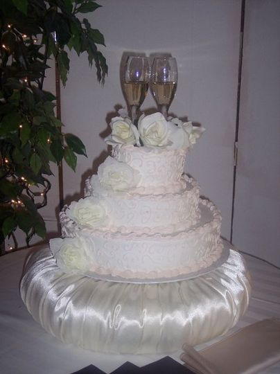 3 tier wedding cake with champaign flute as topper.