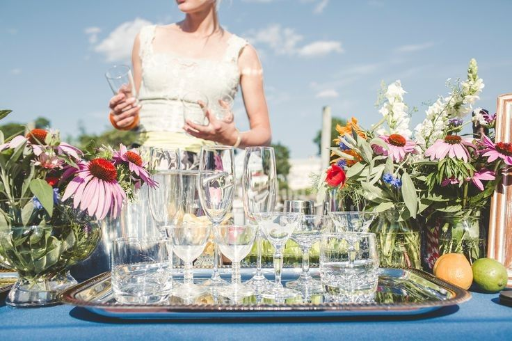Signature cocktail bar with edible garnish bouquets & vintage glassware.