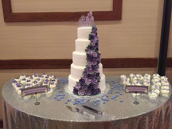 Tall wedding cake with purple flowers