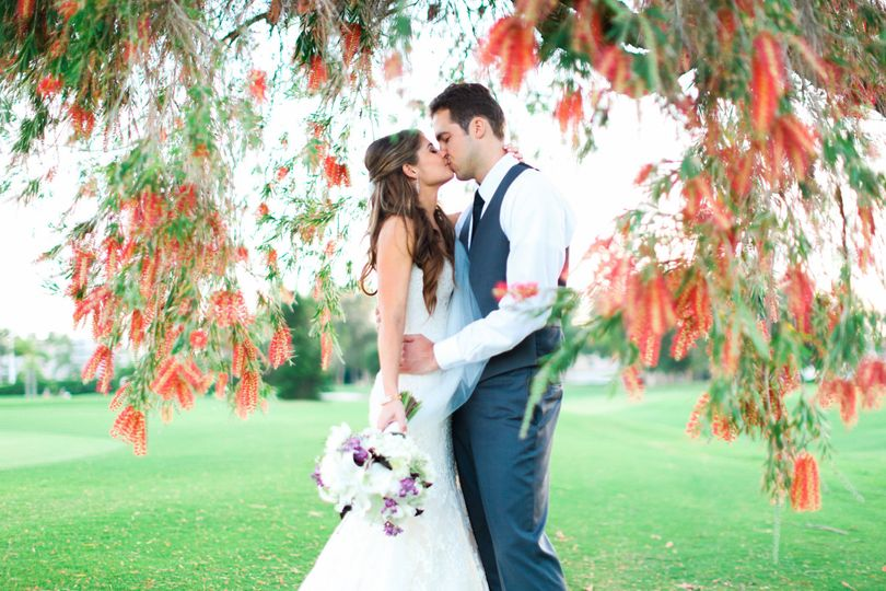 Newlyweds kissing underneath the flowers