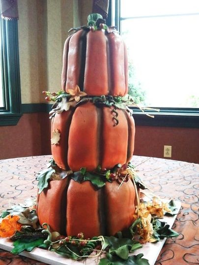 3 pumpkin cakes stacked with gumpaste and fondant leaves and flowers.