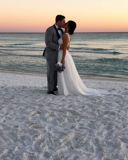 Newlyweds kissing on Henderson Beach