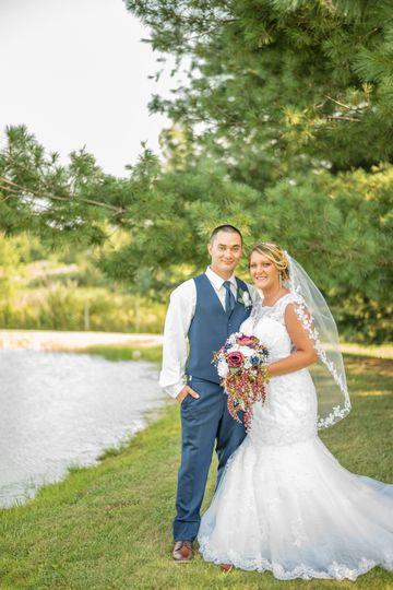Newlywed couple beside a pond