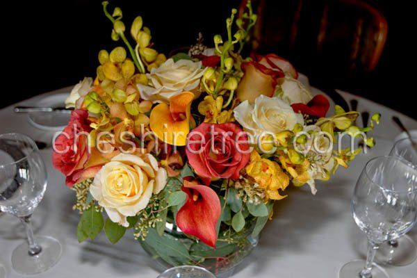 A centerpiece of roses, calla lilies and mokara orchids in sunset colors is perfect for any time of...