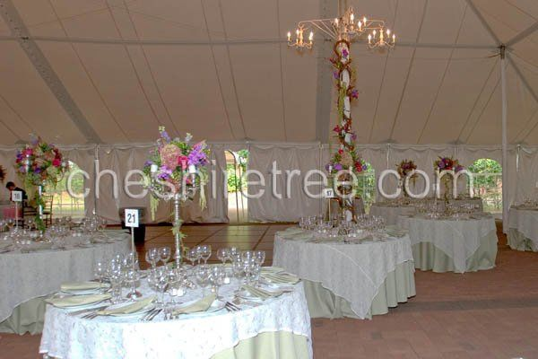 Candelabras and tent pole decoration lend elegance to this wedding at Caramoor Center for the Arts,...