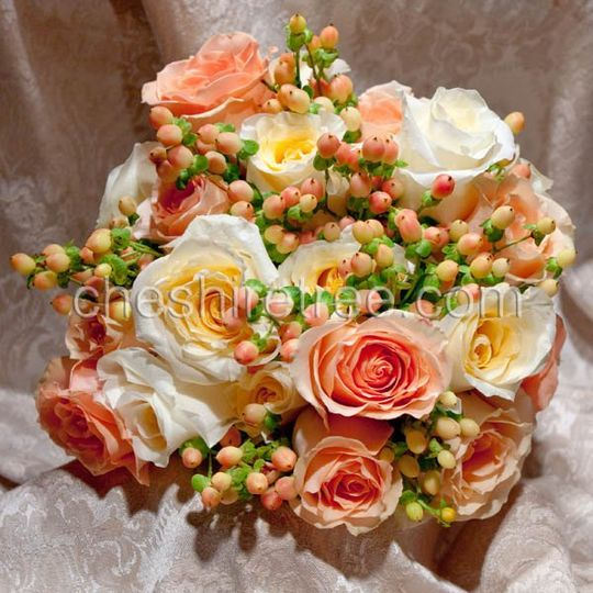 A stem-tied bouquet of yellow and peach roses with hypericum berries. Great for summer of fall...