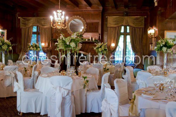 Formal arrangements of orchids, calla lilies and hydrangea float atop a vase filled with white...