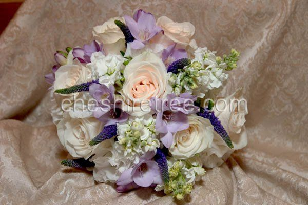 This soft  had-tied bouquet in shade of white ivory, lavender and purple features rosse, mathiola,...