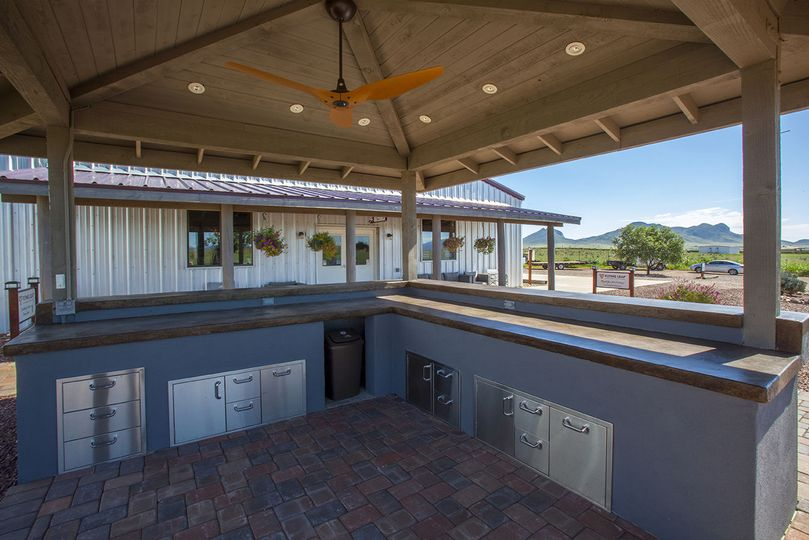 Our outdoor covered patio bar is equipped with a stylish fan, lighting and concrete countertops as...