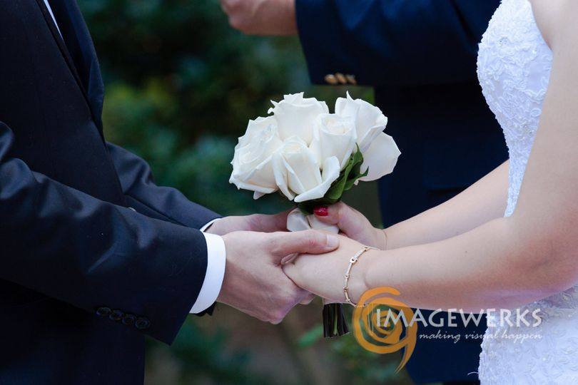 Simple garden ceremony & exchanging of rings. White dress with white rose bouquet.
