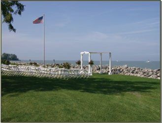 Gazebo set up on Lake Erie shore line with white poly chairs.