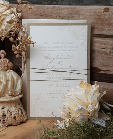 Bouquets and String: The design incorporates custom floral illustrations and letterpress printing on...