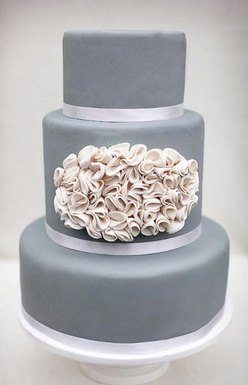 Inspired by a pillow, this cake features gray fondant and ivory ruffles. Can be created in any...