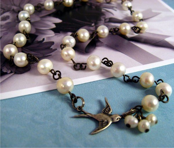 Snowy white freshwater pearls on hand-linked oxidized sterling silver. A silver-plated brass swallow...