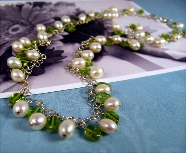 Creamy white freshwater pearls, and peridot gemstones all beaded on to a delicate sterling silver...