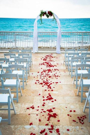 The wedding arch and aisle was decorated with rose petals. This trail of red roses left a wonderful...