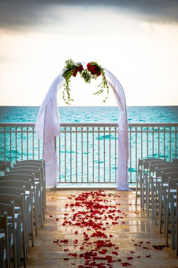 Wedding arch adorned with rose petals. Ceremony is overlooking the ocean as the sky begins to change...