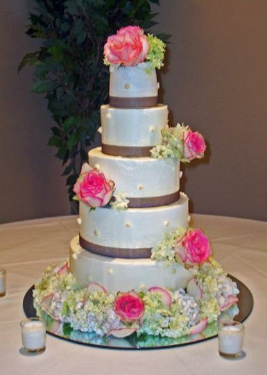 "A beautiful five tiered wedding cake sitting upon a 20"" round mirror.  Chocolate ribbon at the base..."