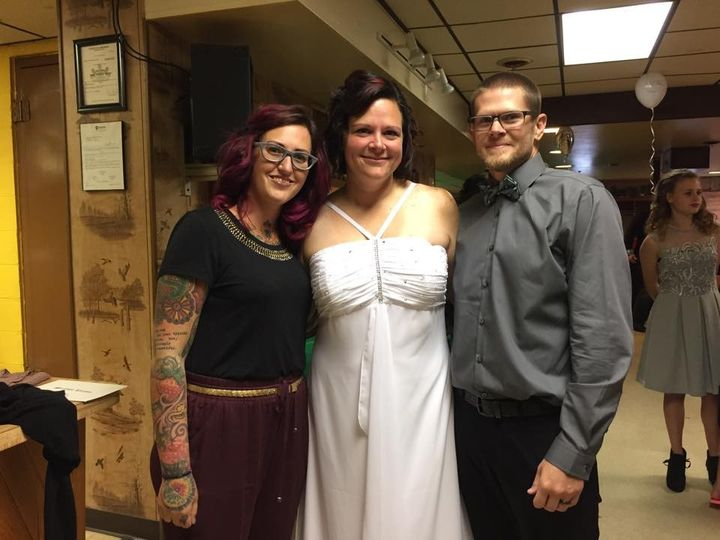 Lovely newlyweds with the officiant