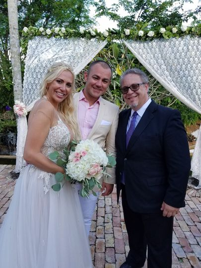 Bride and groom with their wedding officiant