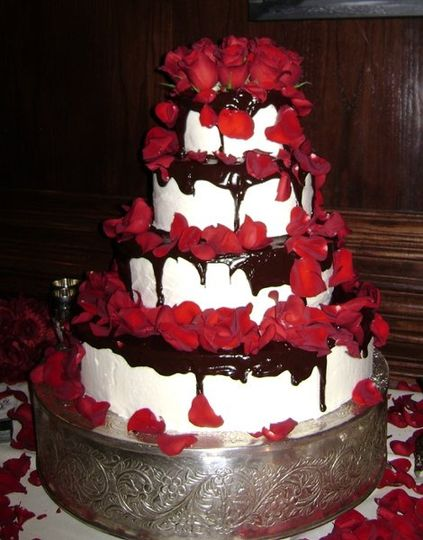 Four-tier round, stacked wedding cake with buttercream icing, chocolate ganache, and red roses.
