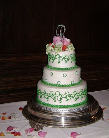 Three-tier round, stacked wedding cake with buttercream icing, decorated with scrolls and fondant...