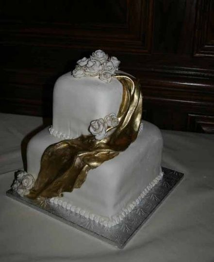 Two-tier, stacked square cake covered in fondant, decorated with gold fondant draping and fondant...