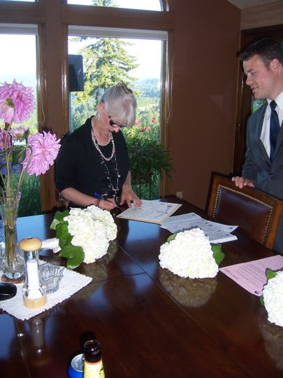 Signing the license, with witnesses observing.
