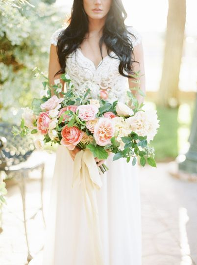 Summer-inspired bridal bouquet with garden roses, dahlias, blueberries and honeysuckle-tied with...