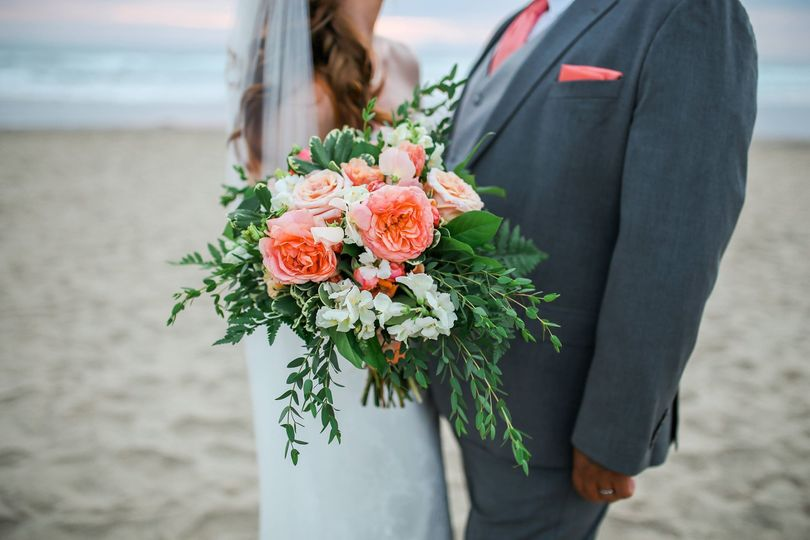 Newlyweds behind their bouquet