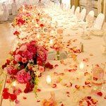 You can decorate a completely white reception venue with bold color roses and candles and have a...