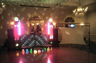 Banquet setup with staging, vertical lighting, and video display