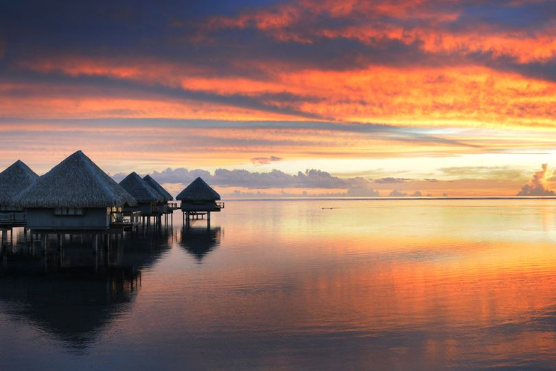 Sunset from an overwater bungalow set the mood for a romantic evening | Honeymoons by Tahiti.com
