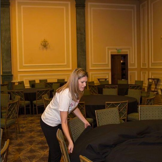 Work in action setting linens for an event