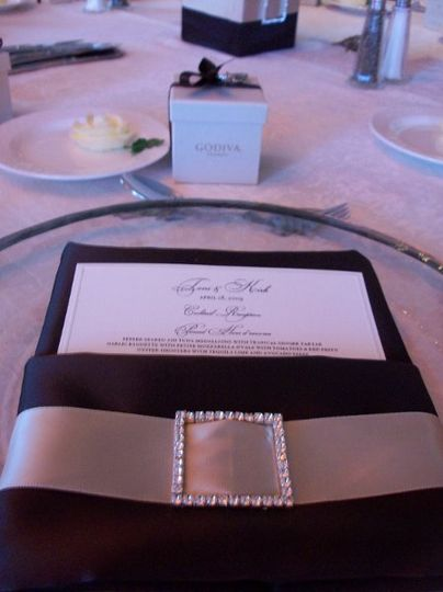 Place setting with satin chocolate napkin and Godiva favors.