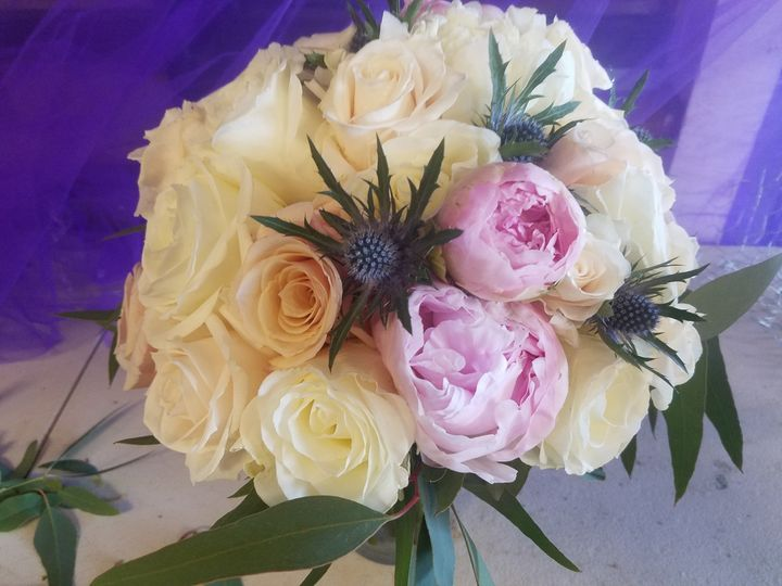 Hand tied bouquet designed with roses, peonies and accents of thistle