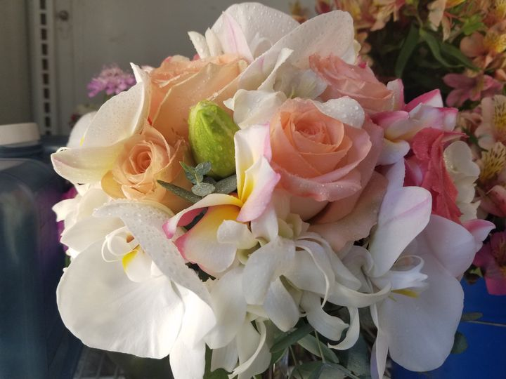Hand tied bouquet of peach roses and white orchids