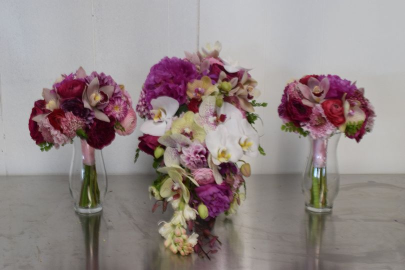 A cascade style bridal bouquet with two bridesmaids bouquets