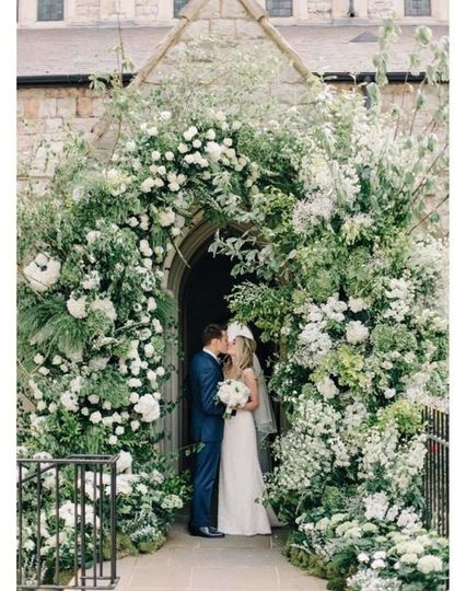Newlyweds kissing under the floral arch
