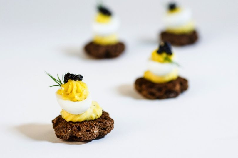 Caviar topped deviled quail egg on pumpernickel star