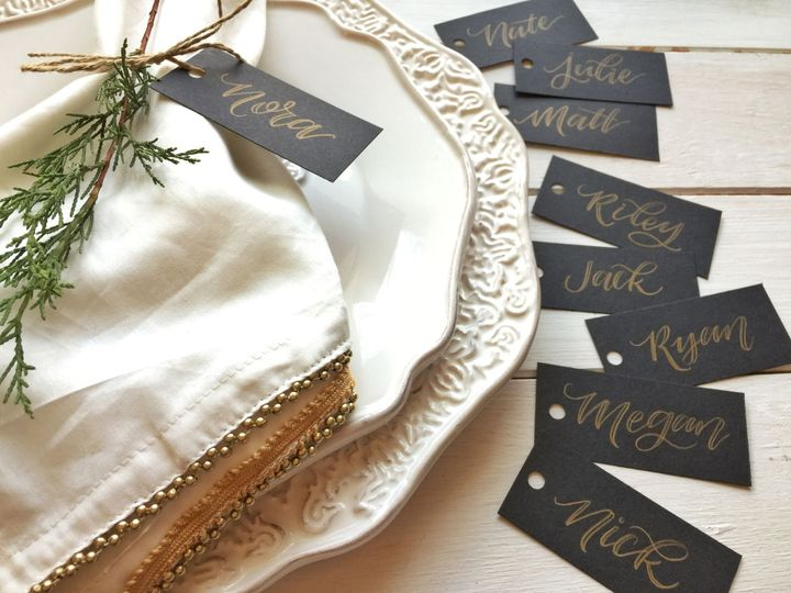 Elegant black name tags with gold calligraphy lettering.