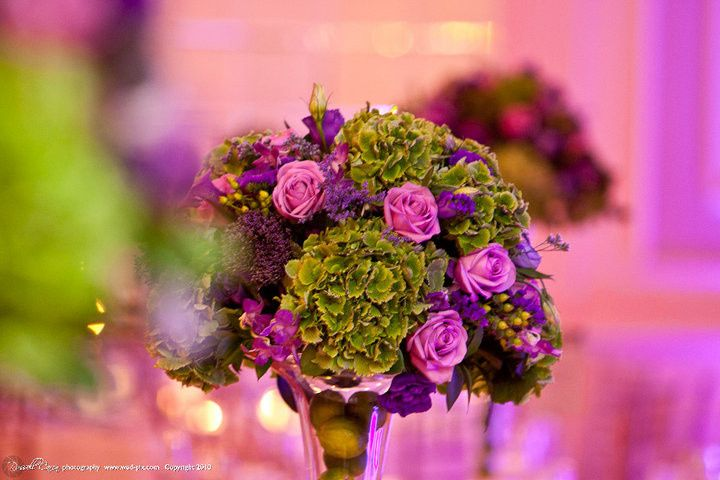 Topiary style centerpiece of lush green hydrangea and purple roses is complimented by fresh limes in...