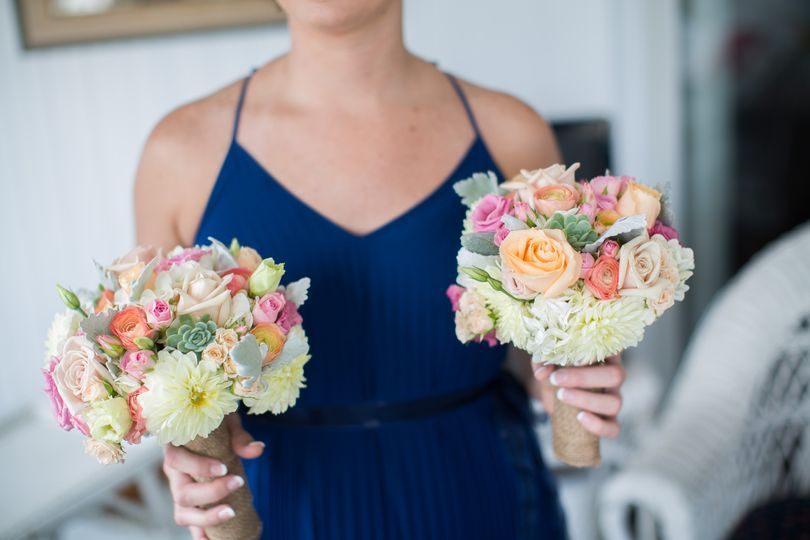Garden roses, dahlias and succulents in subtle tones of pinks, peaches, creams and gray/green are...