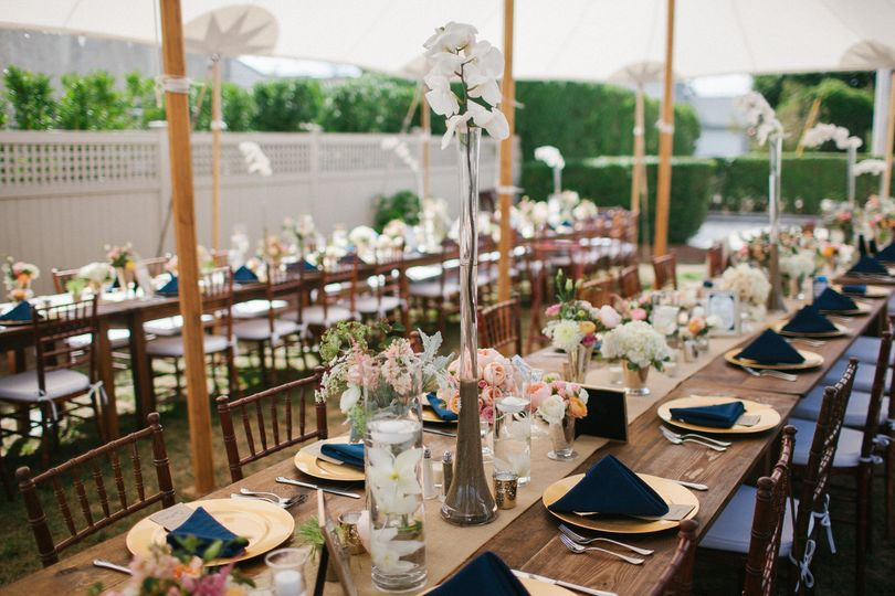 The visual impact of a tablescape centerpiece design of multisized flower clusters, grass tufts,...