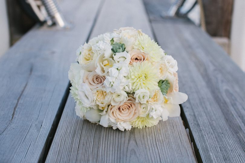 Hand tied bouquet of lush blooms in whites and creams is like a summer breeze.