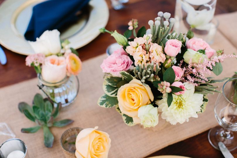 An eye catching array of seasonal summer blooms in pink, peach, cream and gray add to the tablescape...