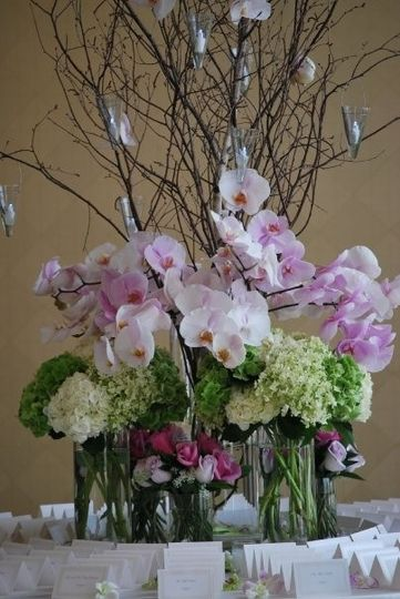 Showy gathering of branches, hanging votive candles, phaelenopsis orchids, hydrangea and roses makes...